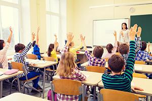 Kids raising their hands in classroom